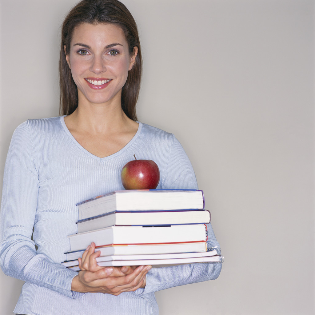 Smiling Teacher Carrying Textbooks and Apple